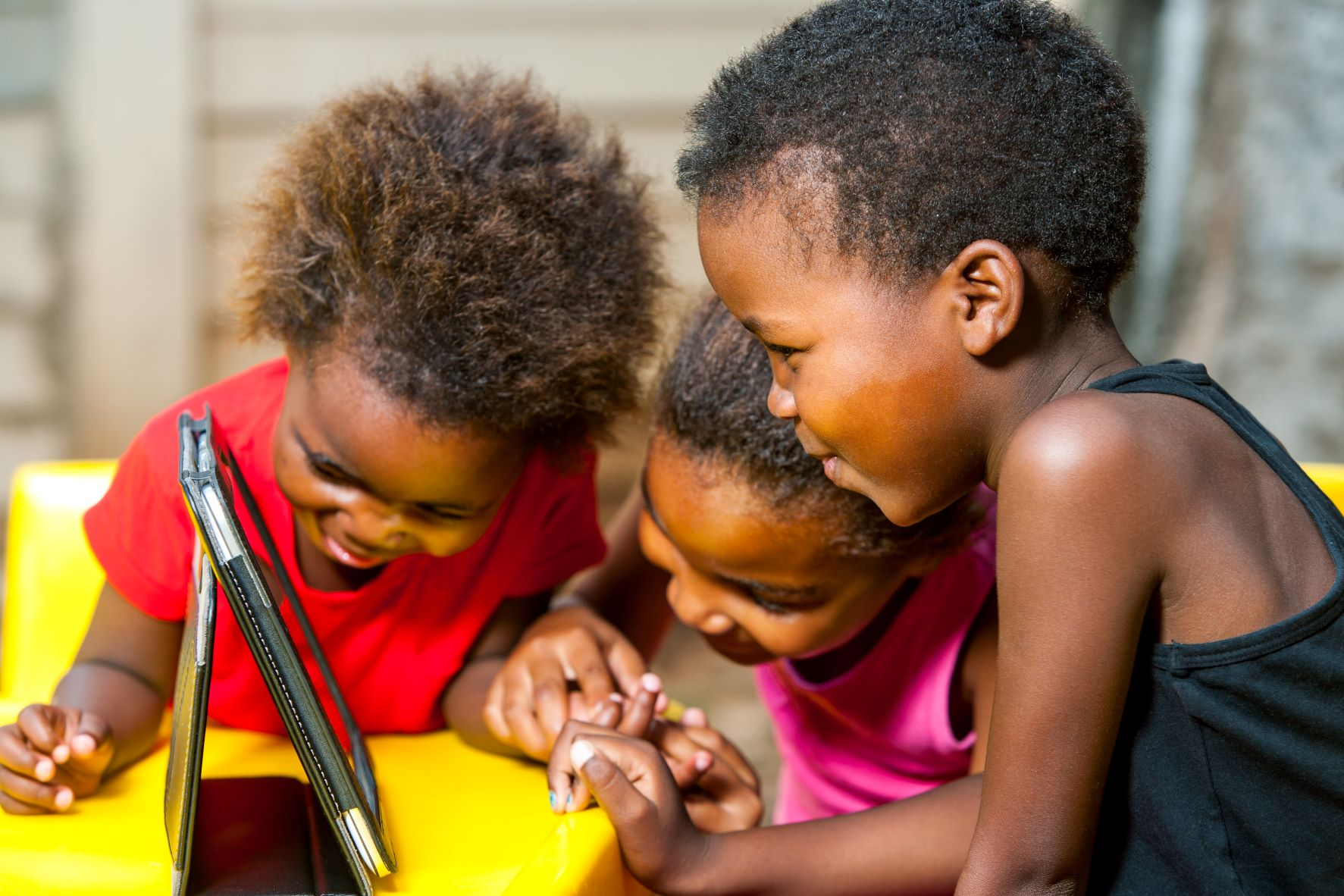 Image of children using the internet on a tablet. USTDA is funding a feasibility study to expand affordable internet access across rural Southern Africa.