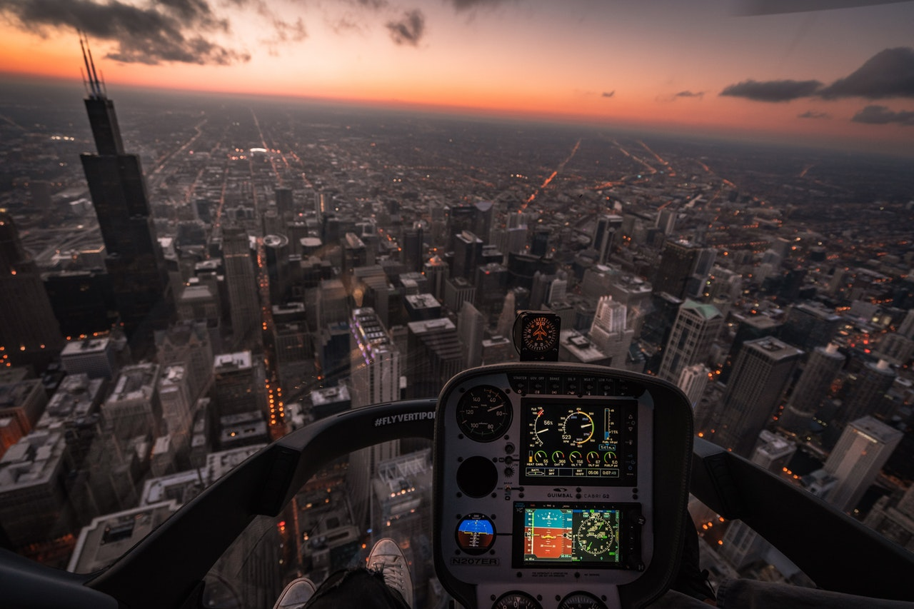 View from within the cockpit of an aircraft flying low over a city skyline