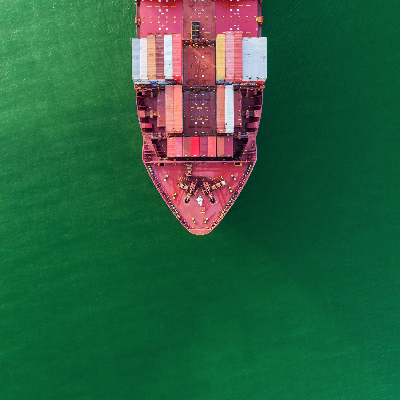 An aerial top-down view of a container ship on the sea going to quayside for load and unload
