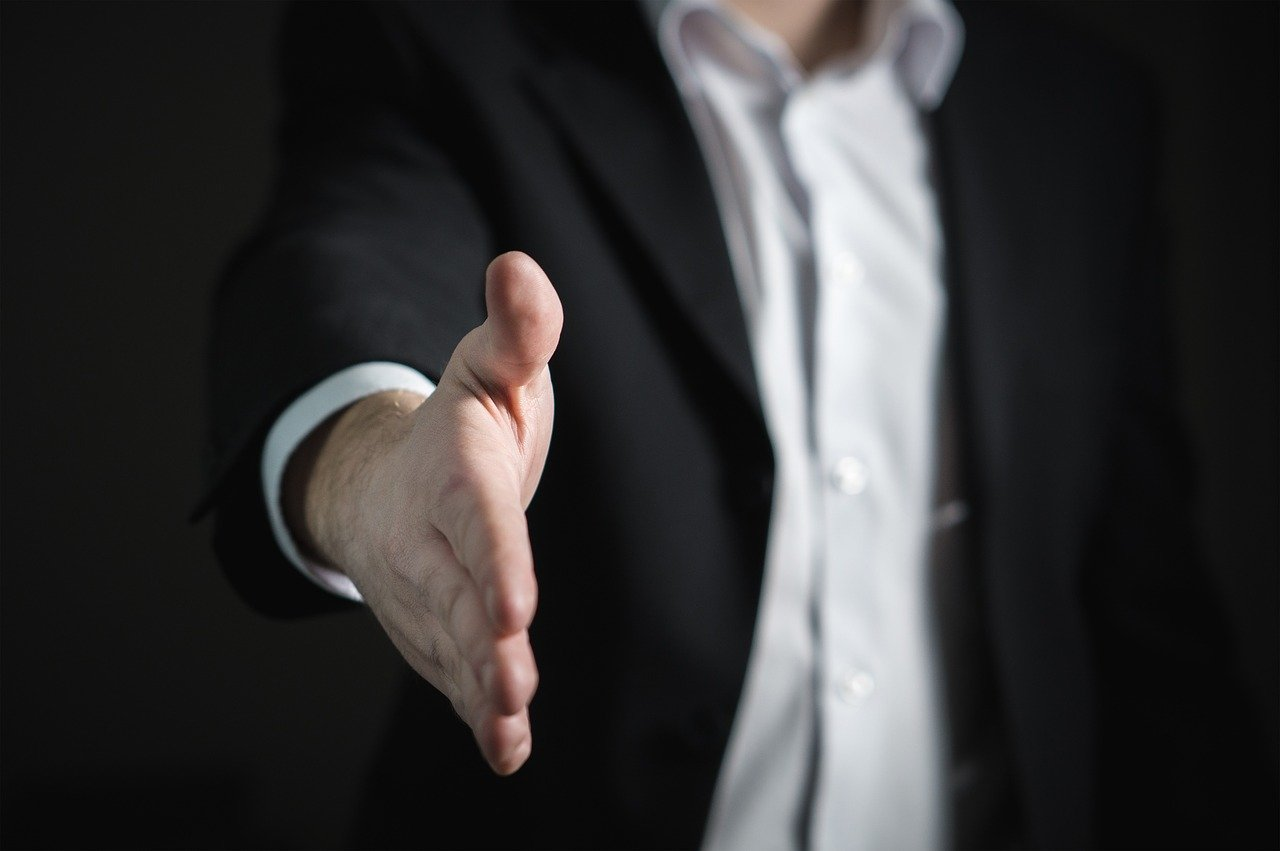 An image of a man in business suit extending hand as if for a handshake.