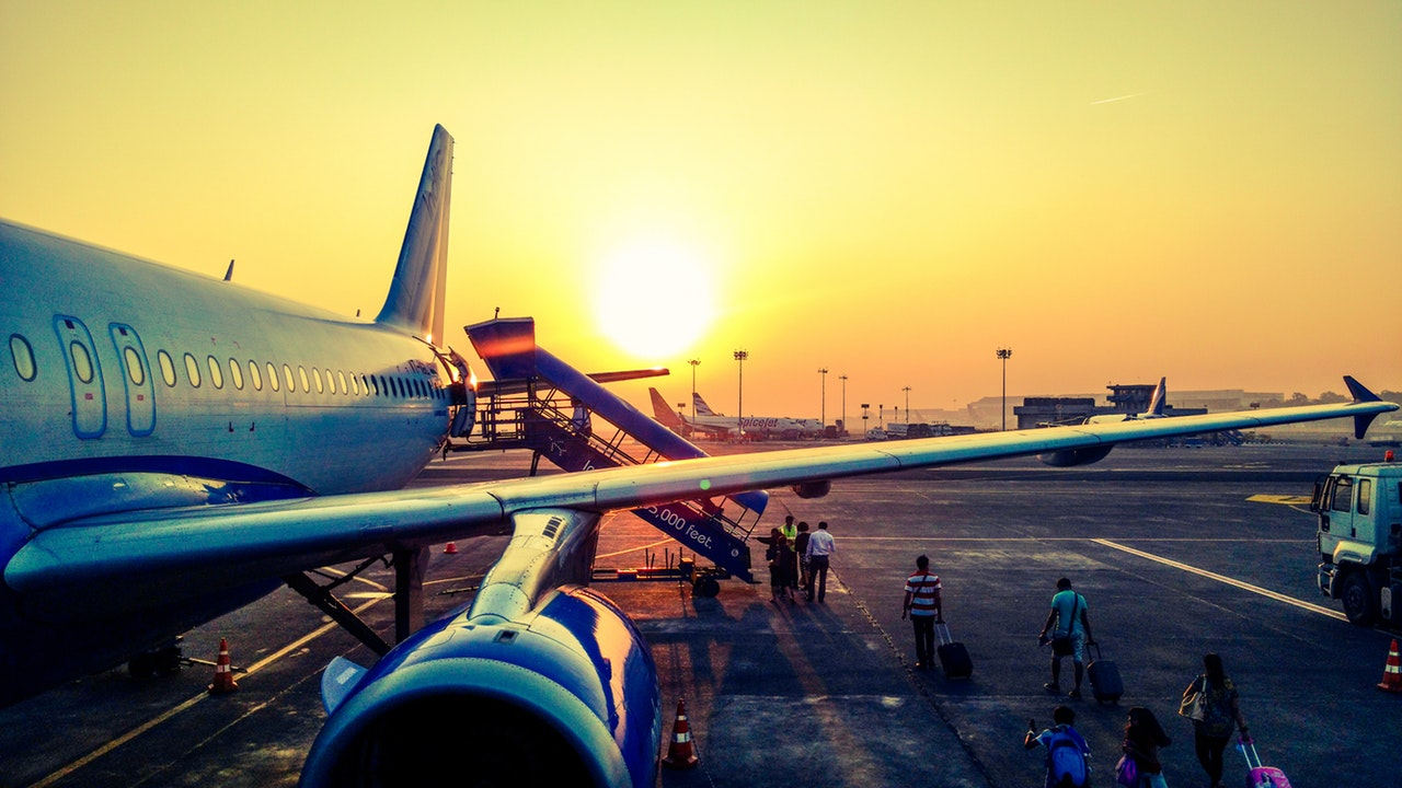 A commercial airliner on the tarmac during sunrise