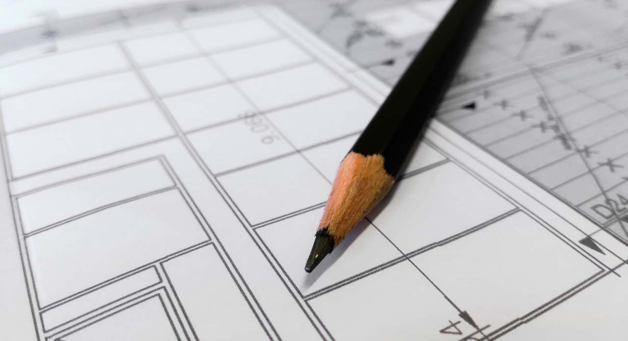 An image of a pencil lying on top of a blueprint page.