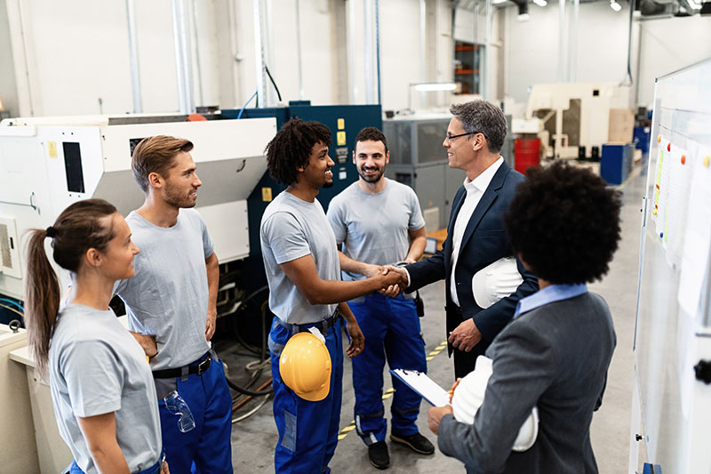 Company manager greeting with African American worker during a tour of his factory workers